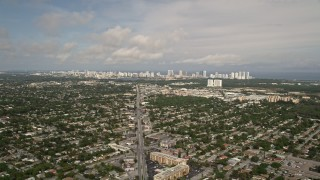 AX0021_002 - 5K stock footage aerial video of suburban area with distant coastal skyscrapers in Sunny Isles Beach, Florida