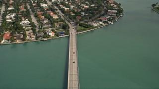AX0021_011E - 5K stock footage aerial video of bird's eye view of light traffic on Broad Causeway, tilt to reveal Bay Harbor Islands neighborhoods, Florida