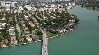 AX0021_012 - 5K stock footage aerial video tilt from Broad Causeway traffic to reveal waterfront community of Bay Harbor Islands, Florida