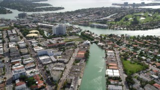 AX0021_020 - 5K stock footage aerial video tilt from waterfront apartment buildings to reveal Normandy Isles, Florida