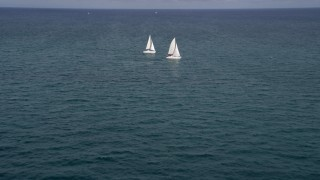 AX0021_037 - 5K stock footage aerial video tilt from calm ocean water to reveal two catamarans near South Beach, Florida