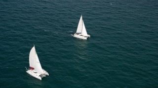 AX0021_038 - 5K stock footage aerial video approach and pass a pair of catamarans sailing the ocean near South Beach, Florida