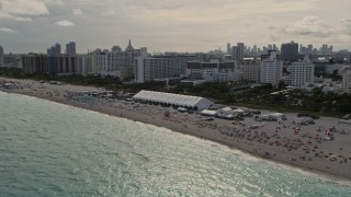 AX0021_052E - 5K stock footage aerial video of beachgoers and oceanfront hotels in Miami Beach, Florida