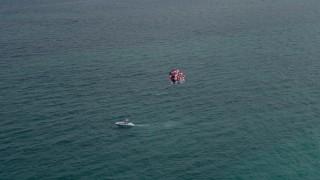 AX0021_054 - 5K stock footage aerial video of parasailer gliding over the ocean near South Beach, Florida
