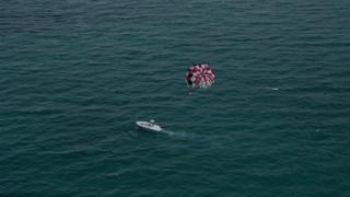 AX0021_055 - 5K stock footage aerial video orbit parasailer gliding over the ocean near South Beach, Florida