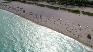 AX0021_057 - 5K stock footage aerial video flyby people on the beach and in the water in South Beach, Florida