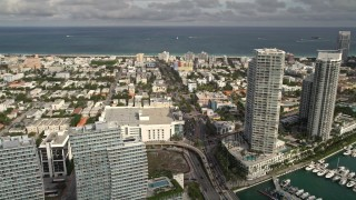 AX0021_063E - 5K stock footage aerial video of slow traffic on the MacArthur Causeway, tilt to condos and marina, South Beach, Florida