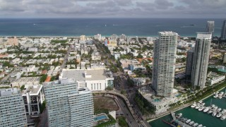 AX0021_064 - 5K stock footage aerial video of residential high-rises by a marina on the shore of South Beach, Florida