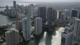 AX0021_080 - 5K stock footage aerial video fly over Miami River to approach high-rise complex in Downtown Miami, Florida