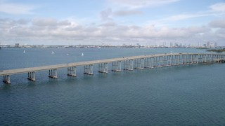 AX0021_112 - 5K stock footage aerial video of bridge on Rickenbacker Causeway with light traffic in Miami, Florida