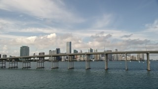 AX0021_112E - 5K stock footage aerial video of Rickenbacker Causeway with light traffic, reveal Downtown Miami skyline, Florida