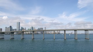 AX0021_113 - 5K stock footage aerial video flyby bridge on Rickenbacker Causeway to reveal Downtown Miami skyline, Florida
