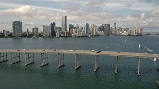 AX0021_115E - 5K stock footage aerial video tilt to reveal and approach Rickenbacker Causeway and Downtown Miami skyline, Florida