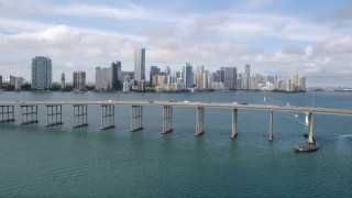 AX0021_116 - 5K stock footage aerial video fly over Rickenbacker Causeway to approach coastal city of Downtown Miami, Florida