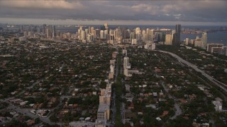 AX0022_024 - 5K stock footage aerial video of following SW 3rd Avenue through suburbs to approach Downtown Miami at sunset, Florida