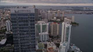 AX0022_043 - 5K stock footage aerial video orbit top of Four Seasons Hotel to reveal waterfront skyscrapers in Downtown Miami at sunset, Florida