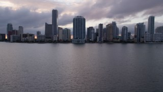 AX0022_056 - 5K stock footage aerial video tilt from bay to reveal and approach Downtown Miami skyline at sunset in Florida