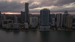 AX0022_056E - 5K stock footage aerial video tilt from bay to reveal and approach Downtown Miami skyline at sunset in Florida