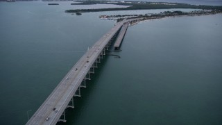 AX0022_072 - 5K stock footage aerial video flyby light traffic crossing bridge on Rickenbacker Causeway at sunset in Florida