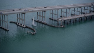 AX0022_073 - 5K stock footage aerial video of sailing boat under a bridge on the Rickenbacker Causeway at sunset in Florida