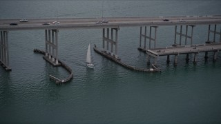 AX0022_073E - 5K stock footage aerial video of sailing boat under a bridge on the Rickenbacker Causeway at sunset in Florida