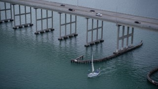 AX0022_074 - 5K stock footage aerial video of tracking sailboat sailing under the Rickenbacker Causeway at sunset in Florida