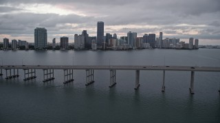 AX0022_076E - 5K stock footage aerial video tilt to reveal and fly over Rickenbacker Causeway to approach Downtown Miami at sunset, Florida