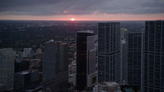 AX0022_088 - 5K stock footage aerial video of the setting sun low on the horizon beyond Downtown Miami skyscrapers, Florida