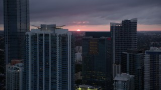AX0022_090 - 5K stock footage aerial video of Downtown Miami skyscrapers and setting sun on horizon in Florida