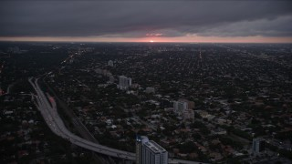 AX0022_093 - 5K stock footage aerial video of Coral Way suburban neighborhoods with setting sun on horizon in Florida