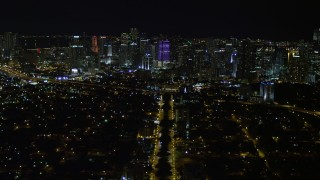 AX0023_003E - 5K stock footage aerial video tilt from SW 3rd Ave to reveal colorful Downtown Miami skyline at night, Florida