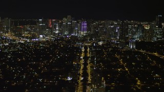 AX0023_004 - 5K stock footage aerial video follow SW 3rd Avenue toward Downtown Miami skyline at night, Florida