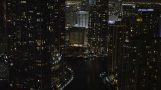 AX0023_037 - 5K stock footage aerial video tilt from bridge to reveal and approach skyscrapers in Downtown Miami at night, Florida