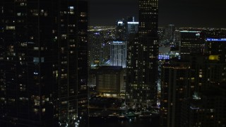 AX0023_037E - 5K stock footage aerial video tilt from bridge to reveal and approach skyscrapers in Downtown Miami at night, Florida