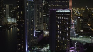 AX0023_048 - 5K stock footage aerial video of InterContinental Miami Hotel at nighttime in Downtown Miami, Florida