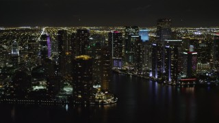 AX0023_058 - 5K aerial stock footage video of Downtown Miami skyscrapers around the Miami River at nighttime in Florida