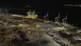 AX0023_060 - 5K stock footage aerial video approach cargo cranes at the Port of Miami at night, Florida