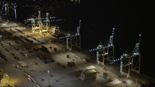 AX0023_061 - 5K stock footage aerial video fly over cranes to approach a cargo ship at the Port of Miami at night, Florida