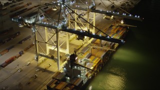 AX0023_062 - 5K stock footage aerial video of two cranes loading a cargo ship at night at the Port of Miami, Florida