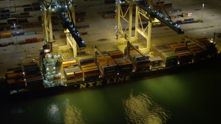 AX0023_062E - 5K stock footage aerial video of two cranes loading a cargo ship at night at the Port of Miami, Florida