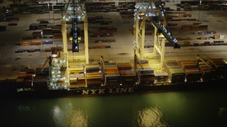 AX0023_063 - 5K stock footage aerial video of cranes unloading a cargo ship docked at the Port of Miami at nighttime, Florida