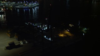 AX0023_064 - 5K stock footage aerial video approach Pilot Boat Docks at the end of the Port of Miami at night, Florida