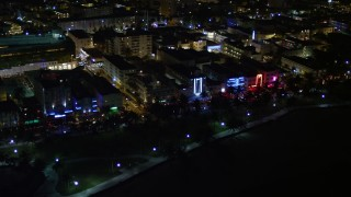 AX0023_071E - 5K stock footage aerial video of hotels and cafes with bright lights at night in South Beach, Florida
