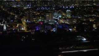 AX0023_073 - 5K stock footage aerial video of Ocean Drive hotels with bright lights at night in South Beach, Florida