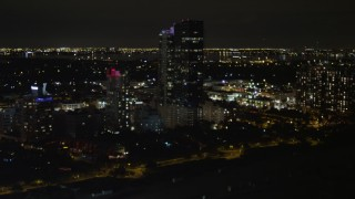 AX0023_080 - 5K stock footage aerial video of passing hotel by the beach at night in Miami Beach, Florida