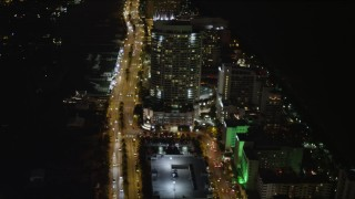 AX0023_085 - 5K stock footage aerial video fly over street by resort hotel at night in Miami Beach, Florida