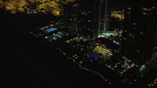AX0023_090 - 5K stock footage aerial video tilt from rooftop to base of Blue and Green Diamonds skyscrapers at night in Miami Beach, Florida