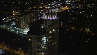 AX0023_093 - 5K stock footage aerial video tilt to the Fontainebleau Miami Beach Resort rooftop at night, Florida