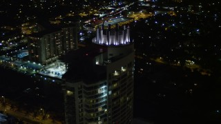 AX0023_093E - 5K stock footage aerial video tilt to the Fontainebleau Miami Beach Resort rooftop at night, Florida