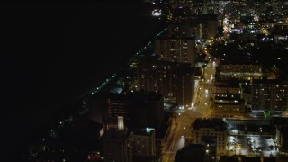AX0023_104 - 5K stock footage aerial video of beachfront condos on Collins Avenue at night in Miami Beach, Florida